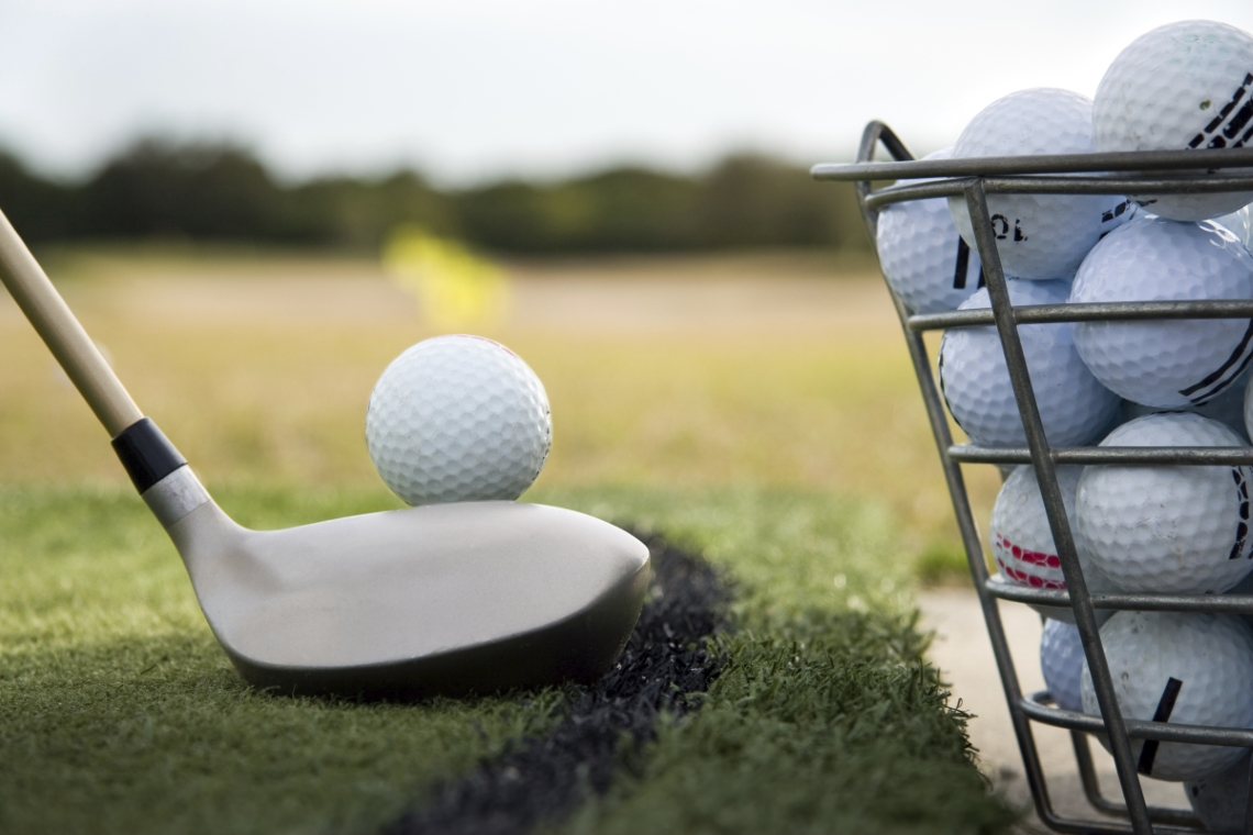 Close up of a golf club preparing to hit a  practice golf ball at a driving range.